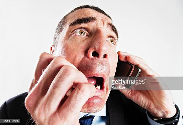 Terrified businessman using cell phone: distorted by fish eye lens