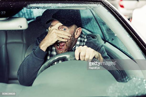 Terrified male driver shields his eyes from probable upcoming collision