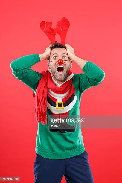 Terrified man in funny winter outfit against red background
