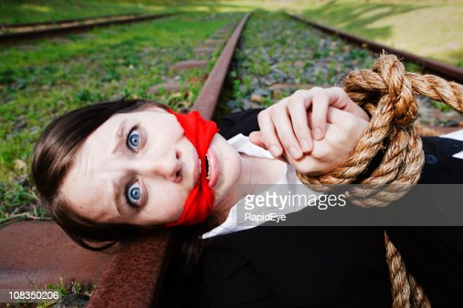 Terrified young woman, gagged and bound, lies on railway tracks