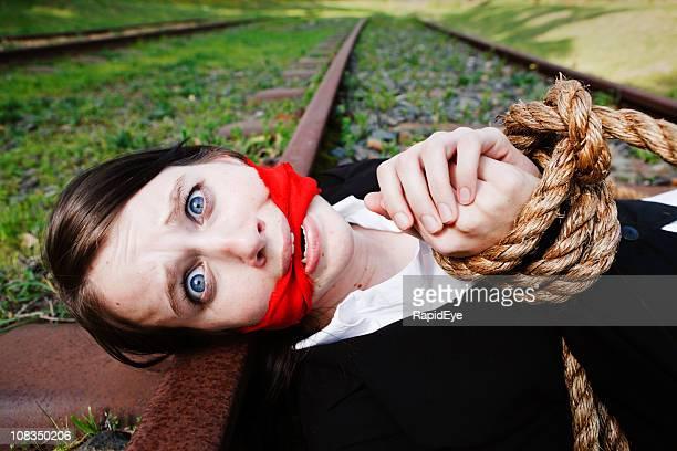 Terrifié jeune femme, gagged et à destination se trouve sur voie ferrée