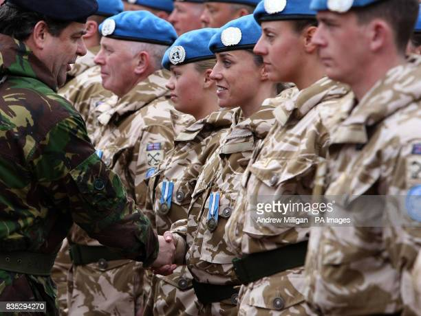 Territorial soldier Lance Corporal Elizabeth Devaney from Crianlaric of the 32 signal regiment group is presented with her United Nations medal by...