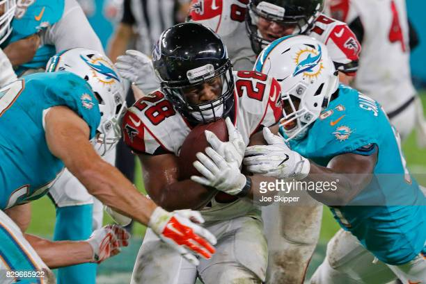 Terron Ward of the Atlanta Falcons is brought down by Joby Saint Fleur of the Miami Dolphins right during their preseason game at Hard Rock Stadium...