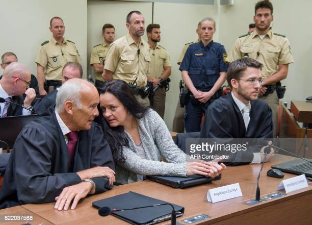 Terror suspect Beate Zschaepe has taken seat between her lawyers Mathias Grasel and Hermann Borchert after arriving in a courtroom for another...