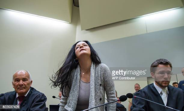 Terror suspect Beate Zschaepe takes seat between her lawyers Mathias Grasel and Hermann Borchert as she arrives in a courtroom for another session of...