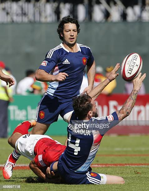 Terry Bouhraoua is tackles by Santiago Avarez of Argentina as French rigby player Vincent Inigo looks on during their rugby match on the first day of...