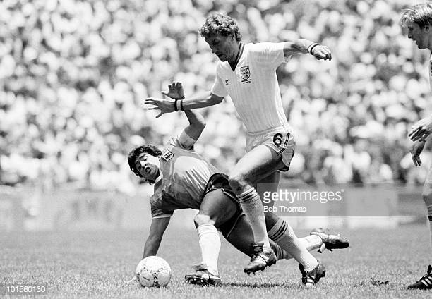 Terry Butcher of England challenges for the ball against Diego Maradona of Argentina during their World Cup QuarterFinal match held at the Azteca...