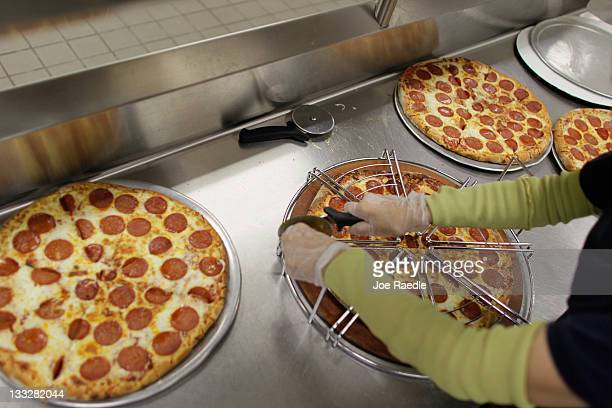 Terry Cheung cuts a pizza pie into slices as she prepares to serve it to students at Everglades High School on November 18 2011 in Miramar Florida...