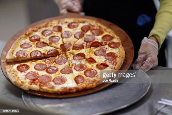 Terry Cheung prepares a pizza pie to be served to students at Everglades High School on November 18 2011 in Miramar Florida Monday evening the United...