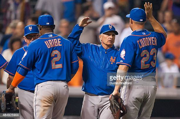 Terry Collins of the New York Mets celebrates the win over the Colorado Rockies with Juan Uribe and Michael Cuddyer after a game Coors Field on...