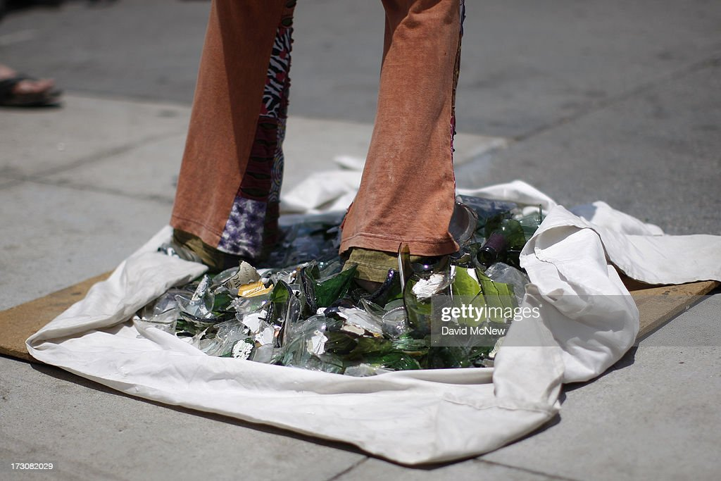 Terry Hernandez, a street performer from Trinidad Tobago, stands barefoot on shards of broken glass on Independence Day weekend at Venice Beach on July 6, 2013 in Venice, California. An estimated 16 million people visit the famous beach city annually which is celebrating 108th birthday as of July 4.