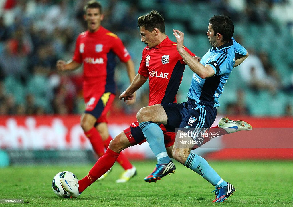 Terry McFlynn of Sydney tackles Evan Kostopoulos of Adelaide as he shoots for goal during the round eight A-League match between Sydney FC and Adelaide United at Allianz Stadium on November 23, 2012 in Sydney, Australia.