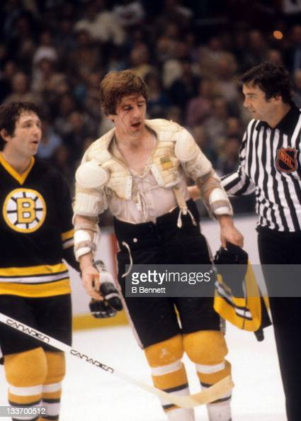 Terry O'Reilly of the Boston Bruins is helped over to the penalty box after being involved in a fight as Brad Park talks with the linesman during a...