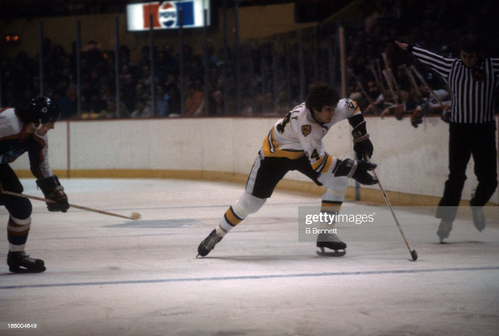 Terry O'Reilly of the Boston Bruins skates with the puck during an NHL game against the New York Rangers circa 1977 at the Boston Garden in Boston...