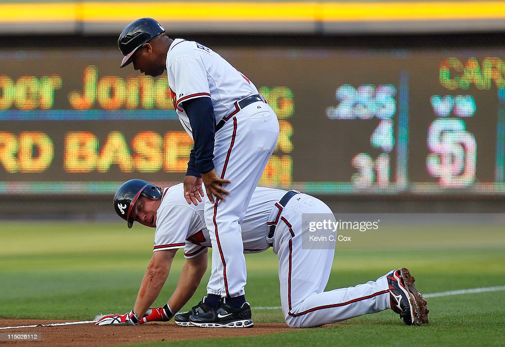 Terry Pendleton #9 tends to Chipper Jones #10 of the Atlanta Braves after Jones tripped over Brad Hawpe #11 of the San Diego Padres in the first inning at Turner Field on June 1, 2011 in Atlanta, Georgia.