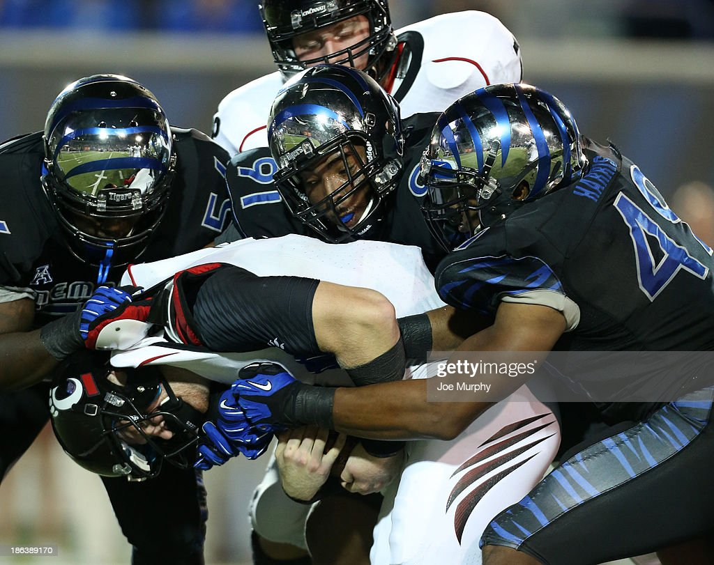 Terry Redden #56, Ricky Hunter #91 and Charles Harris #49 of the Memphis Tigers tackle Jordan Luallen #10 of the Cincinnati Bearcats on October 30, 2013 at Liberty Bowl Memorial Stadium in Memphis, Tennessee.