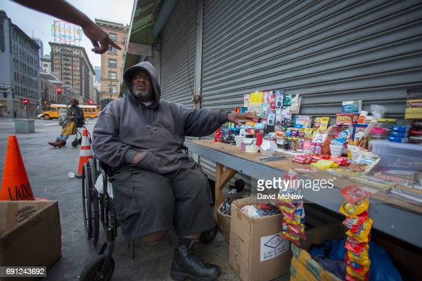 Terry ÔYogiÕ Walker who has lived on Skid Row since the 1970s serves a homeless customer from his sidewalk store that stays open all night when...
