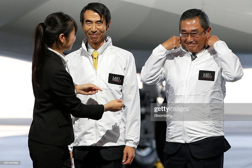 <a gi-track='captionPersonalityLinkClicked' href=/galleries/search?phrase=Teruaki+Kawai&family=editorial&specificpeople=11273516 ng-click='$event.stopPropagation()'>Teruaki Kawai</a>, president of Mitsubishi Aircraft Corp., center, and <a gi-track='captionPersonalityLinkClicked' href=/galleries/search?phrase=Shinichiro+Ito&family=editorial&specificpeople=5666038 ng-click='$event.stopPropagation()'>Shinichiro Ito</a>, president and chief executive officer of ANA Holdings Inc., right, smiles as they attend a rollout ceremony for the Mitsubishi Regional Jet (MRJ) passenger aircraft, developed by Mitsubishi Aircraft Corp., at Mitsubishi Heavy Industries Ltd.'s Nagoya Aerospace Systems Works Komaki South Plant in Toyoyama, Aichi Prefecture, Japan, on Saturday, Oct. 18, 2014. Japan unveiled its first passenger jet today after a delay of almost four years, with a helping hand from bullet-train specialists as it prepares for test flights next year. Photographer: Kiyoshi Ota/Bloomberg via Getty Images
