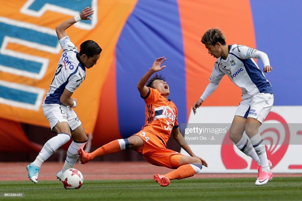 Teruki Hara of Albirex Niigata is tackled by Yosuke Ideguchi (L) of Gamba Osaka during the J.League J1 match between Albirex Niigata and Gamba Osaka at Denka Big Swan Stadium on April 1, 2017 in Niigata, Japan.