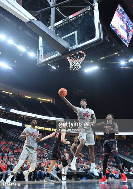 Tervell Beck of the UNLV Rebels drives in for a layup against Donnie Tillman of the Utah Utes as Brandon McCoy of the UNLV Rebels and Jayce Johnson...