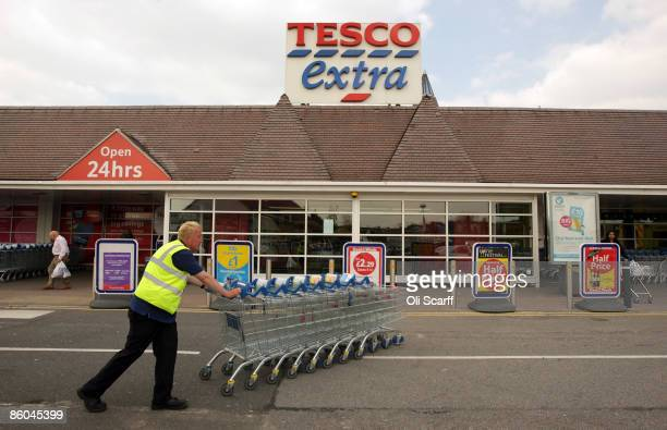 Tesco employee pushes a stack of trolleys past the entrance to the Tesco Extra superstore on April 20 2009 in New Malden Surrey England The huge New...
