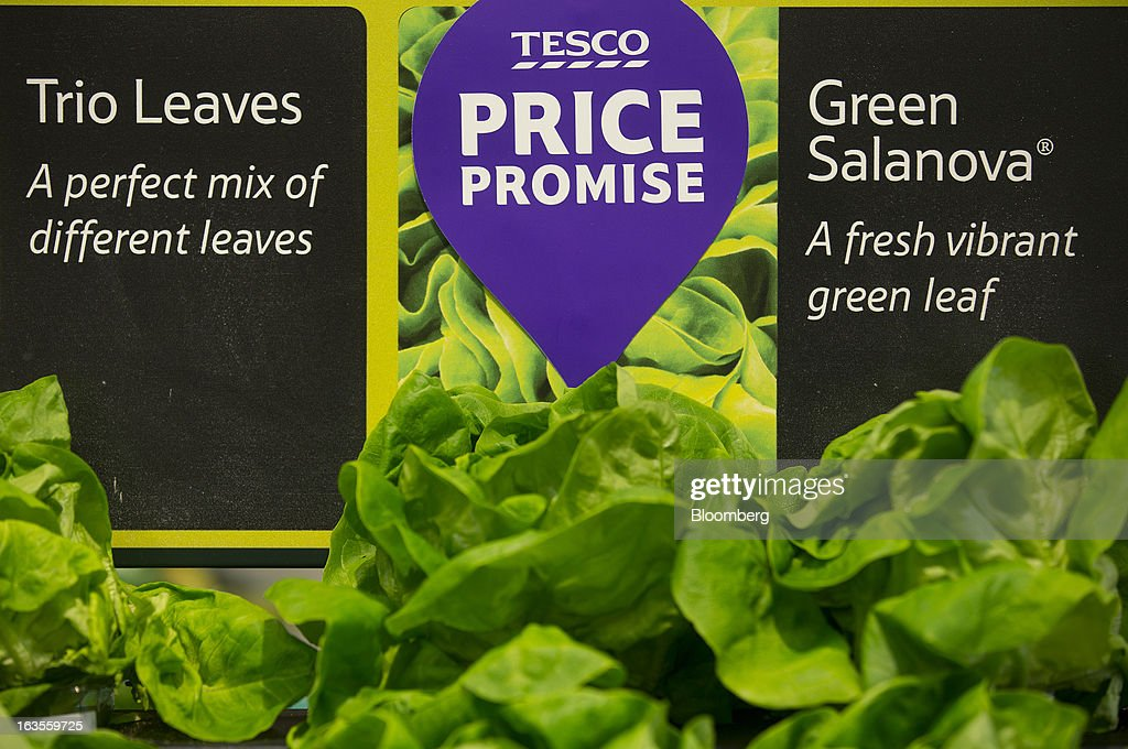 A Tesco 'Price Promise' logo sits on a display of lettuce in the fruit and vegetable section of a Tesco Plc supermarket in the borough of Kensington in London, U.K., on Tuesday, March 12, 2013. Tesco Plc, the U.K.'s largest grocer launched a 'Price Promise', its latest initiative offering to match the price of customers' purchases to that of it's rivals, including Wal-Mart Stores Inc.'s ASDA. Photographer: Simon Dawson/Bloomberg via Getty Images