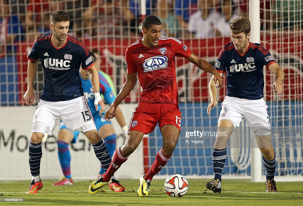 Tesho Akindele #13 of FC Dallas tries to maneuver the ball past Stephen McCarthy #15 and Patrick Mullins #7 of New England Revolution at Toyota Stadium on July 19, 2014 in Frisco, Texas.