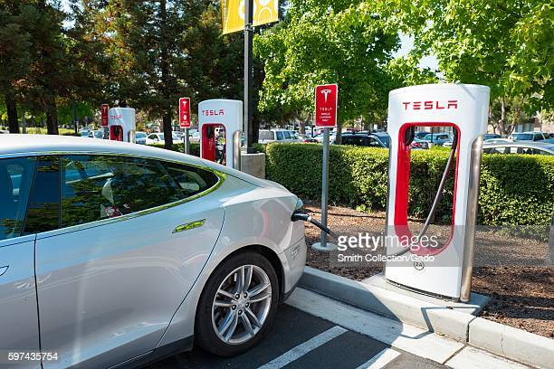 Tesla automobile plugged in and charging a Supercharger rapid battery charging station for the electric vehicle company Tesla Motors in the Silicon...