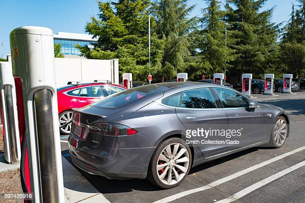 Tesla automobile plugged in and charging at a Supercharger rapid battery charging station for the electric vehicle company Tesla Motors in the...