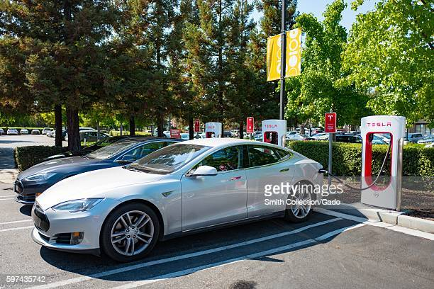 Tesla automobiles plugged in and chargging at a Supercharger rapid battery charging station for the electric vehicle company Tesla Motors in the...