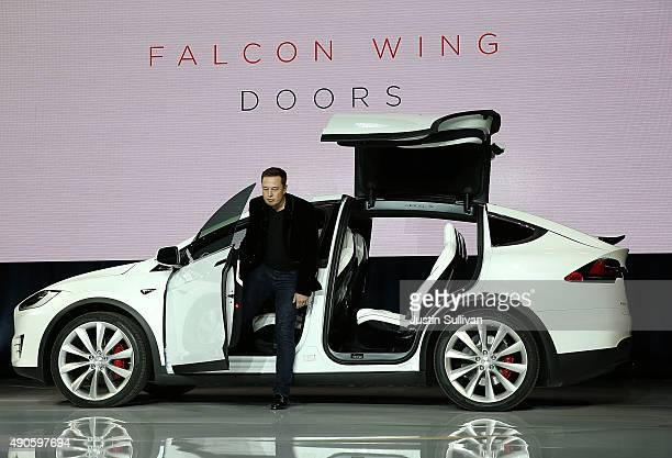 Tesla CEO Elon Musk demonstrates the falcon wing doors on the new Tesla Model X Crossover SUV during a launch event on September 29 2015 in Fremont...