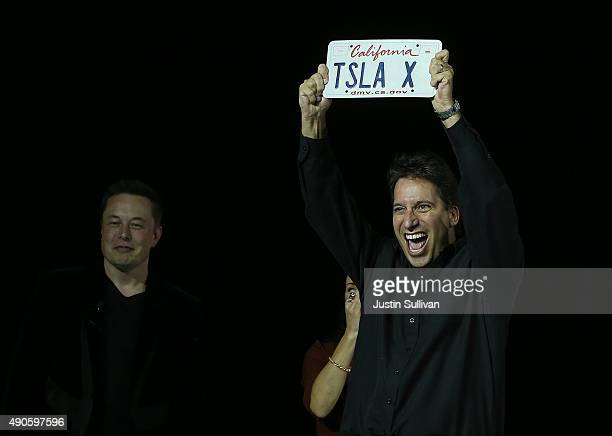 Tesla CEO Elon Musk looks on as the first person to take delivery of the new Tesla Model X Crossover SUV holds up a vanity license plate on September...