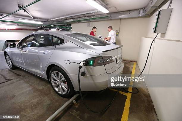 A Tesla electric vehicle manufactured by Tesla Motors Inc sits recharging in a parking lot at the headquarters of Yandex NV during the launch of the...