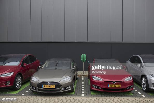 A Tesla Model S second left and a Tesla Model 3 automobile second right stand by an electrical charging point outside the Tesla Motors Inc factory in...