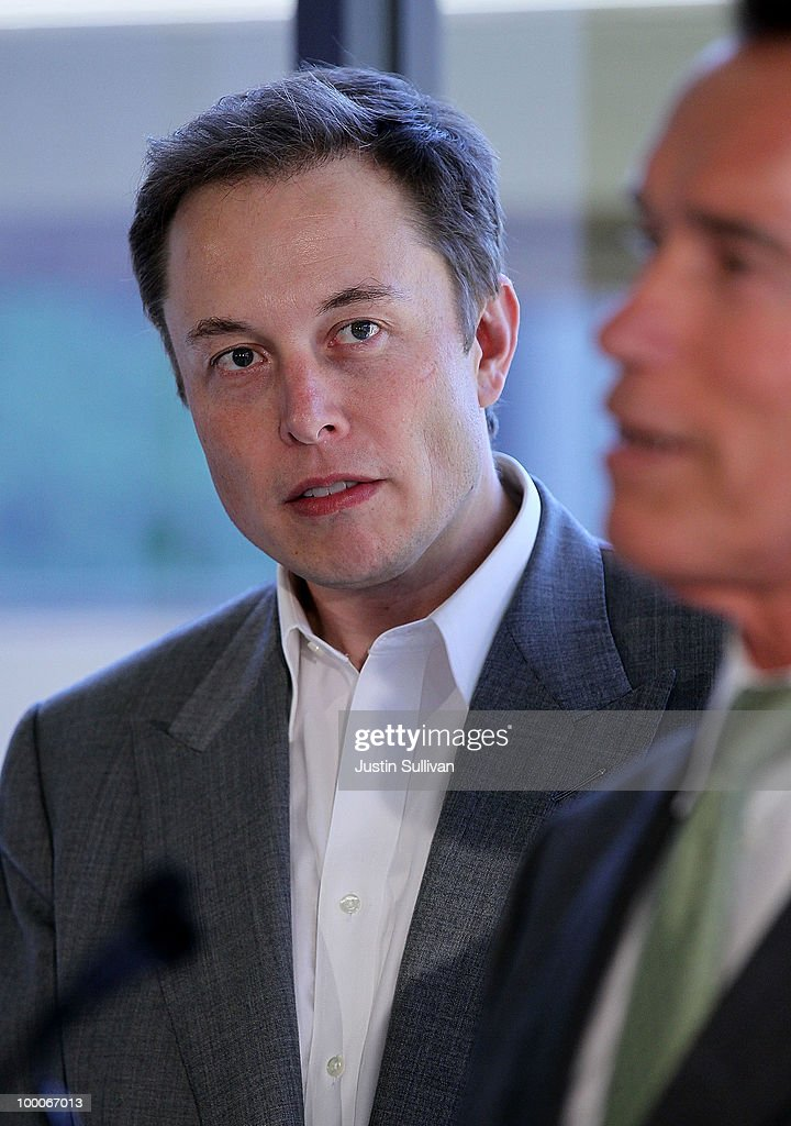 Tesla Motors CEO Elon Musk look on as California governor Arnold Schwarzenegger speaks during a news conference at Tesla Motors headquarters May 20, 2010 in Palo Alto, California. Electric car maker Tesla Motors annoucned a partnership with Japanese automaker Toyota to make electric cars in the United States. The cars will be manufactured at the recently shuttered NUMMI plant in Fremont, California where Toyota had pulled out after a joint partnership with General Motors had ended.