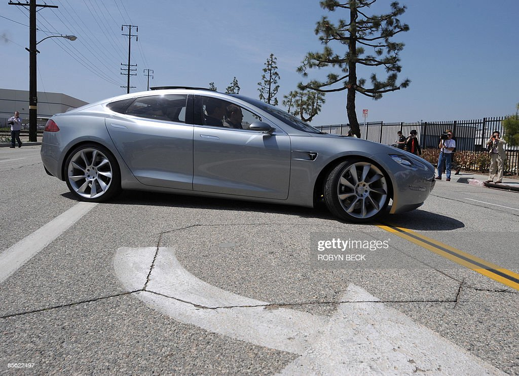 Tesla Motors Chairman and CEO Elon Musk (in driver's seat) and chief designer Franz von Holzhausen (in passenger seat) drive the new Tesla Model S all-electric sedan as members of the media look on, at the car's unveiling in Hawthorne, California on March 26, 2009. Musk said the state-of-the-art, five-seat sedan will be the world's first mass-produced, highway-capable electric car. The car has an anticipated base price of 57,400 US dollars but will cost less than 50,000 after a federal tax credit of 7,500 dollars. AFP PHOTO / Robyn BECK
