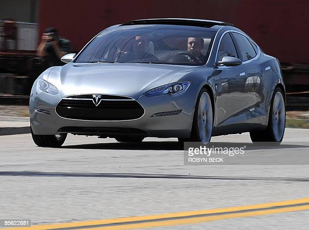 Tesla Motors Chairman and CEO Elon Musk and chief designer Franz von Holzhausen drive the new Tesla Model S allelectric sedan out into the street as...