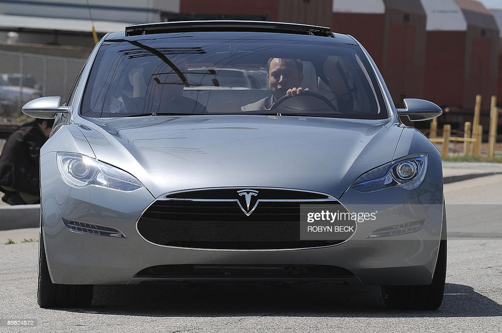 Tesla Motors Chairman and CEO Elon Musk (in driver's seat) and chief designer Franz von Holzhausen (L) drive the new Tesla Model S all-electric sedan, in Hawthorne, California on March 26, 2009. Musk said the state-of-the-art, five-seat sedan will be the world's first mass-produced, highway-capable electric car. The car has an anticipated base price of 57,400 US dollars but will cost less than 50,000 after a federal tax credit of 7,500 dollars. AFP PHOTO / Robyn BECK