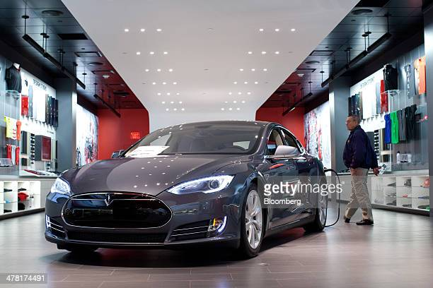 A Tesla Motors Inc Model S connected to a charger sits on display at the company's store at the Short Hills Mall in Short Hills New Jersey US on...