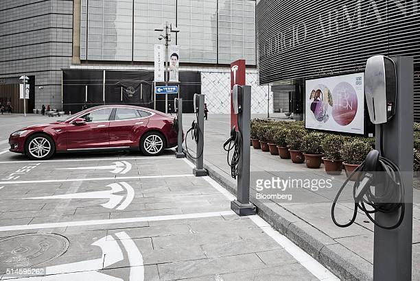 A Tesla Motors Inc Model S electric automobile sits parked at one of the company's electric charging stations near a shopping mall in Beijing China...