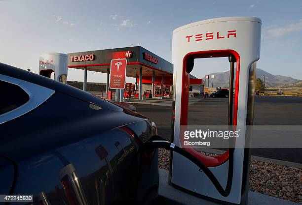 A Tesla Motors Inc Model S P85D vehicle sits plugged in at a charging station near a Texaco Inc gas station in Nephi Utah US on Tuesday April 7 2015...