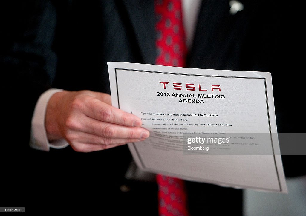 A Tesla Motors Inc. representative reviews an agenda for the company's annual meeting in Mountain View, California, U.S., on Tuesday, June 4, 2013. Elon Musk, co-founder and chief executive officer of Tesla Motors Inc., said stores will expand to 50 from 34 this year and the service network is expected to double by year-end. Photographer: Noah Berger/Bloomberg via Getty Images