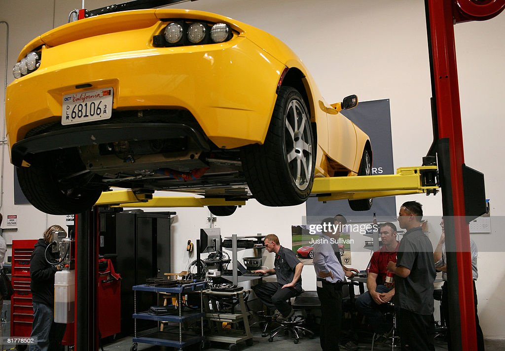 Tesla Motors vehicle technicians stand under a Tesla Roadster after a news conference with California governor Arnold Schwarzenegger June 30, 2008 at Tesla Motors in San Carlos, California. Governor Schwarzenegger announced that electric car company Tesla Motors will build a new manufacturing facility in California to manufacture its all-electric Tesla Roadster. The $109,000 2009 Tesla Roadster zero emissions vehicle is capable of traveling nearly 250 miles on a single charge and is capable of going 0-60 miles per hour in 3.9 seconds.