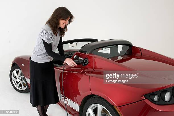 Tesla Roadster electric car being charged Artist Unknown