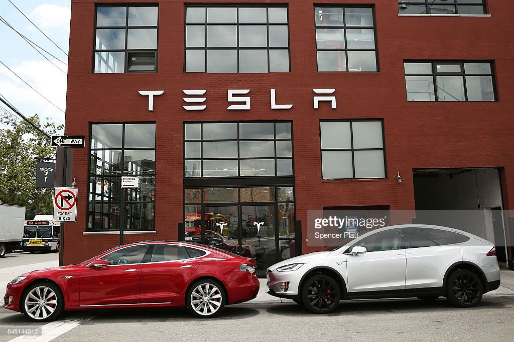 Tesla vehicles sit parked outside of a new Tesla showroom and service center in Red Hook Brooklyn on July 5 2016 in New York City The electric car...