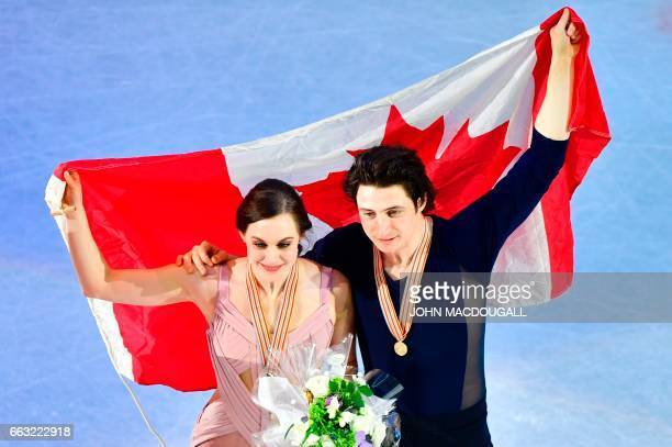 Tessa Virtue and Scott Moir of Canada pose with their national flag after winning the Ice Dance / Free Dance event at the ISU World Figure Skating...