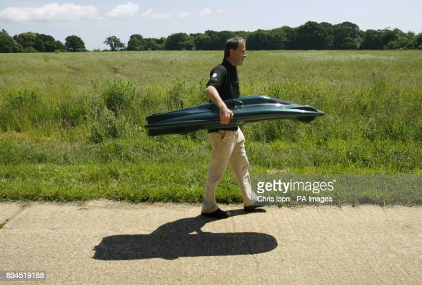 Test driver Don Wales carrying a scale model of the British Steam Car currently under construction in the New Forest Hampshire