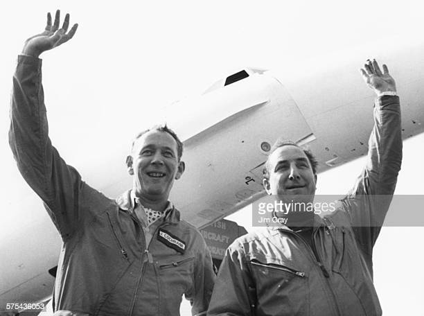 Test pilot Brian Trubshaw and his copilot John Cochrane smiling and waving after flying the successful maiden flight of the Concorde 002 at RAF...