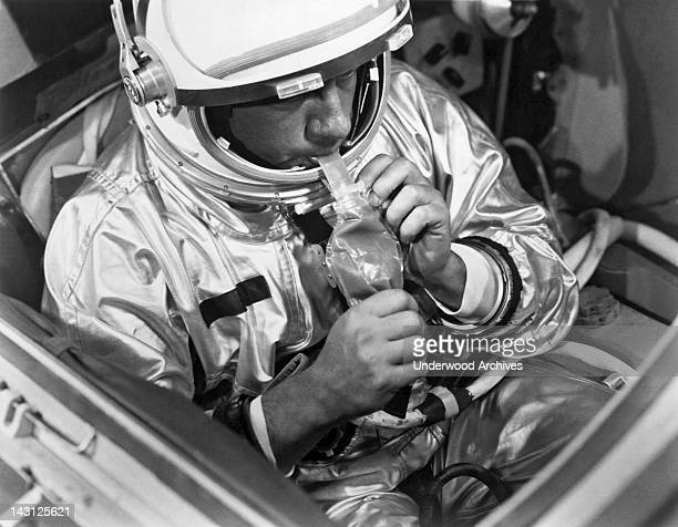 A NASA test subject consumes a meal of pot roast and gravy through a feeding tube pack aboard a Gemini spacecraft mockup Houston Texas March 1966