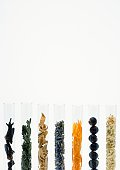 Test tubes containing dried flowers, berries and spices